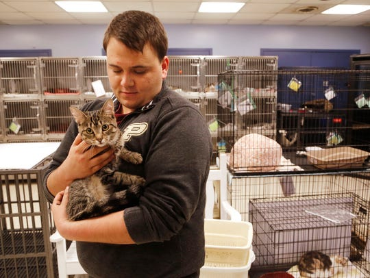 Andrew DeMarco cuddles Chicken, a one-year-old domestic