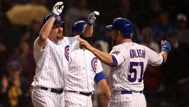 Chicago Cubs starting pitcher Travis Wood (left) celebrates with left fielder Ryan Kalish (51) after hitting a three-run home run against the Arizona Diamondbacks during the second inning at Wrigley Field on April 21, 2014.