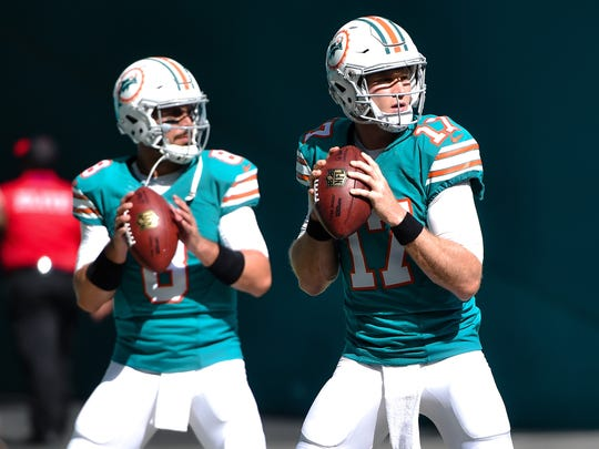 Nov 27, 2016; Miami Gardens, FL, USA; Miami Dolphins quarterback Matt Moore (left) and Dolphins quarterback Ryan Tannehill (right) both warm up before their game against San Francisco 49ers at Hard Rock Stadium. Mandatory Credit: Steve Mitchell-USA TODAY Sports