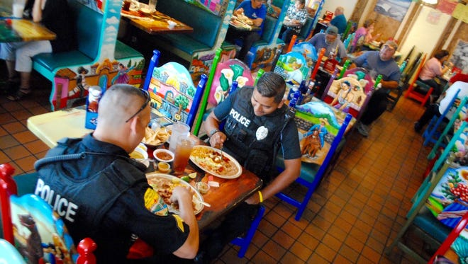 Anthony police officers Jon Gutierrez, left and Orlando Flores join a growing lunch crowd at Delicias Cafe.