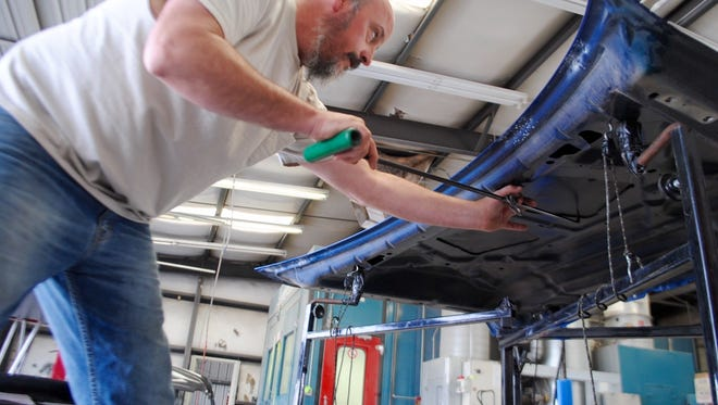 With pressure, torque, time and patience, auto hail repair specialist Trey Pool works last week to correct damage caused by recent hail storms in Las Cruces.