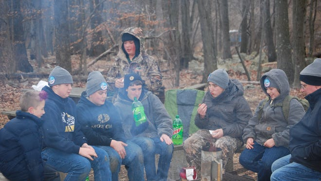 Boy Scouts from Troop 112 of Alexandria gather around the campfire after a hard day of work organizing the Klondike Derby at the Teetertown Preserve in Califon.