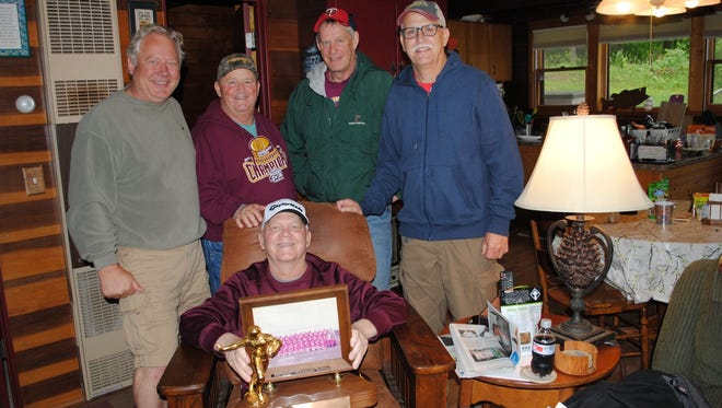 The 1974 conference championship football team from Luverne has its trophy back. Jon Bot (sitting with trophy) is surrounded by Pete Olsen (left),  Keith Cook, Perry Noll and Peter Eberlein last week at Olsen's cabin in northern Minnesota.