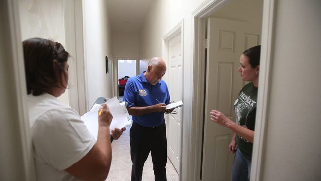 Carlos Madrigal, Loss Verifier agent for the Federal Disaster at center and Theresa Gonzales, emergency services coordinator for the CAL OES takes notes on damaged from Jessica Tucker, Tucker's home was flooded in the La Quinta Cove.