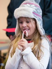 Madi Elfreich-Leap, 8, enjoys her candy cane from Santa after seeing him at the West Side Nut Club's 18th annual Santa Land on Sunday afternoon.