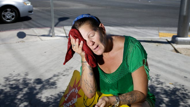 Amanda Ouellet wipes her face with a cold, wet towel to cool off while holding an advertising sign  July 1, 2014, in Las Vegas. Nevada had its warmest year on record in 2014.