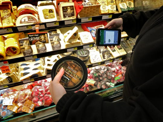 Courtney Jeanpierre scans an item for a customer's online grocery order at Albrecht's Delafield Market. The smartphone app will confirm whether the correct item was selected and add the cost of the item to the customer's invoice.