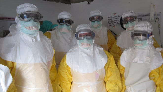 In this undated handout photo provided by Medecins Sans Frontieres, local staff and health care workers for Doctors Without Borders wear Ebola protection equipment in Liberia.