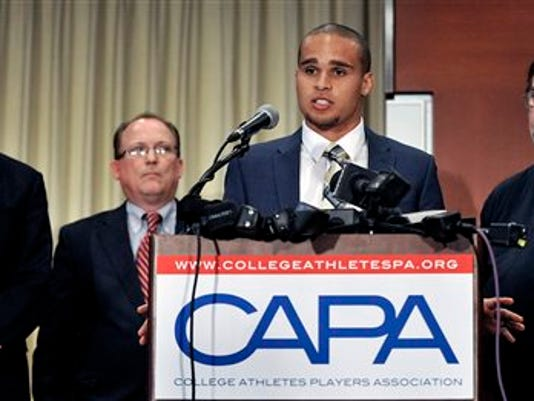 In this Jan. 28, 2014, file photo, Northwestern quarterback Kain Colter second from right, speaks while College Athletes Players Association president Ramogi Huma left, United Steel Workers National Political Director Tim Waters second from left, and United Steel Workers president Leo Gerard right, look on during a news conference in Chicago. The National Labor Relations Board has dismissed a historic ruling that Northwestern University football players are school employees who are entitled to form what would be the nation's first union of college athletes. The NLRB released its decision Monday. The losing side does not have an option to appeal.