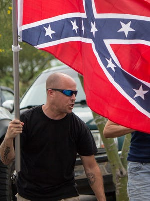 Jon Ritzheimer waves a Confederate flag outside a west Phoenix Walmart on Sunday, July 5, 2015.