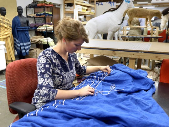 Sandy Wickert embroiders a costume that will be worn