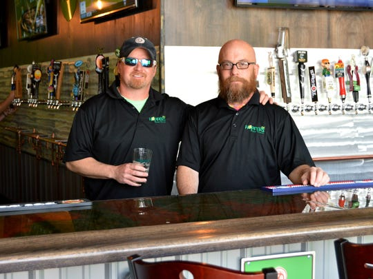 Glenn Ains and Hopper's Tap House bar manager Blake Benn stand behind the bar.