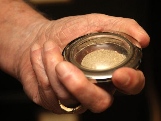Veteran Don Burgett clutches a vial of sand from Utah beach embedded in an engraved silver memento.