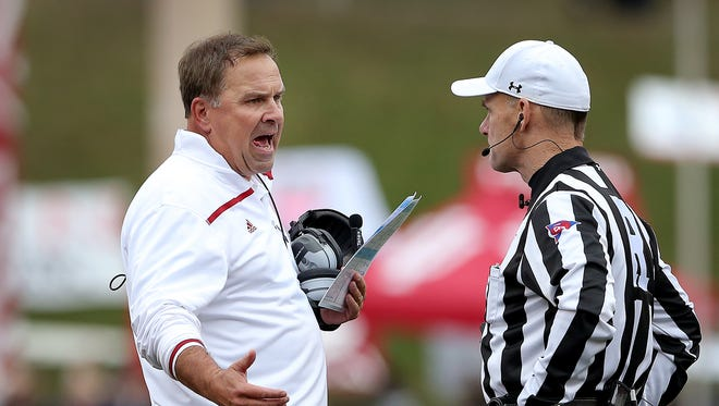 Former Indiana Hoosiers head coach Kevin Wilson (left) argues a call with NCAA referee John O'Neill.