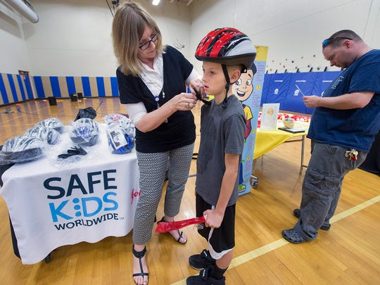 From the left, Helen Lehman, a coordinator for Safe Kids York County, fits Hayden Myers, age 10, of Windsor with a bike helmet while his father, Eric, waits.
