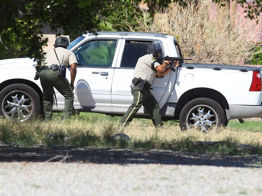 Peace officers point to a home on Cypress Road after