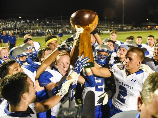 Cedar Crest hoists The Cedar Bowl trophy after defeating Lebanon 26-14 in the annual Cedar Bowl last season.