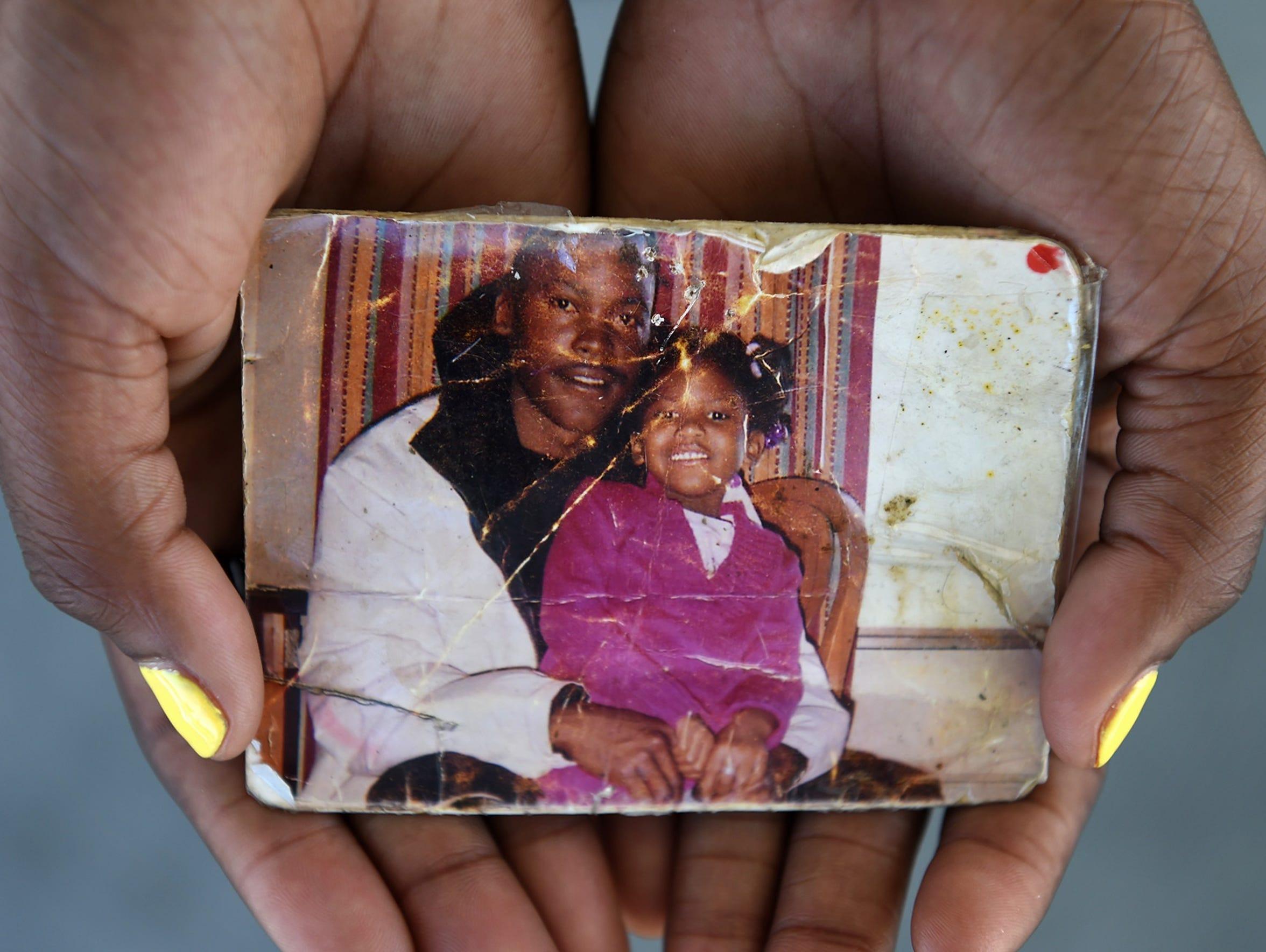 Davi'Ana Kirkland, 17, holds a photograph of her and