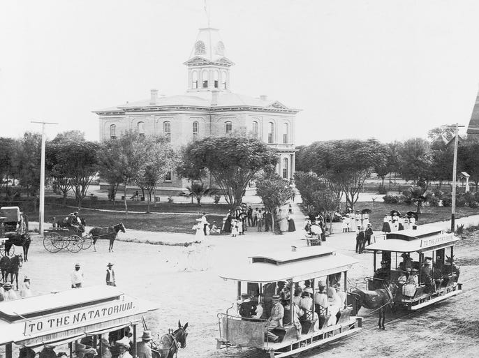 """THEN: Horse-drawn streetcars pass by the old courthouse in Phoenix in the late 1890s. The sign on the street car, """"To the Natatorium,"""" refers to an indoor swimming pool."""