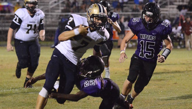 Eau Gallie QB Devan Lormand tries to get past George Allen (22) and Elizah Easton (15) of Space Coast during Friday's game at Space Coast Jr/Sr High.