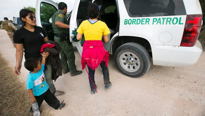 A group of two Honduran women and two young children sit get into a Border Patrol SUV in the U.S. Fish and Wildlife Refuge near the Anzalduas International Bridge not far from the Rio Grande river in Mission, Tex., on Saturday, June 21, 2014. The women say they crossed the Rio Grande river from Mexico into Texas early that morning. They were apprehended by Game Wardens from Texas Parks & Wildlife Department.