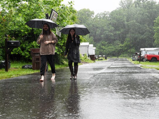 Colby Young and Kayla Barnes walk in the rain after