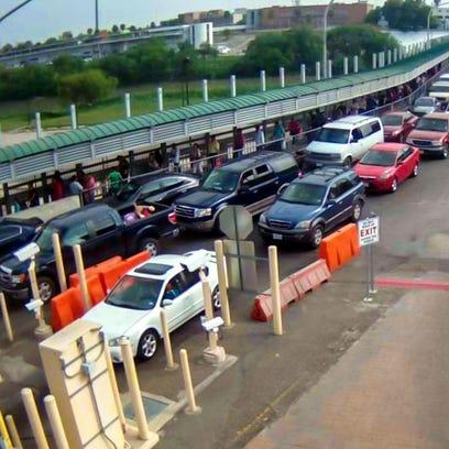 Fila de autos en el puerto de entrada a EU por Nuevo