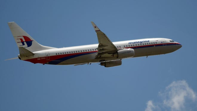 A Malaysia Airlines Boeing 737 jet flies over the Sukarno-Hatta airport in Tangerang. The airline continues to use flight number 17 from Amsterdam to Kuala Lumpur, despite one of its jets being shot down Thursday.