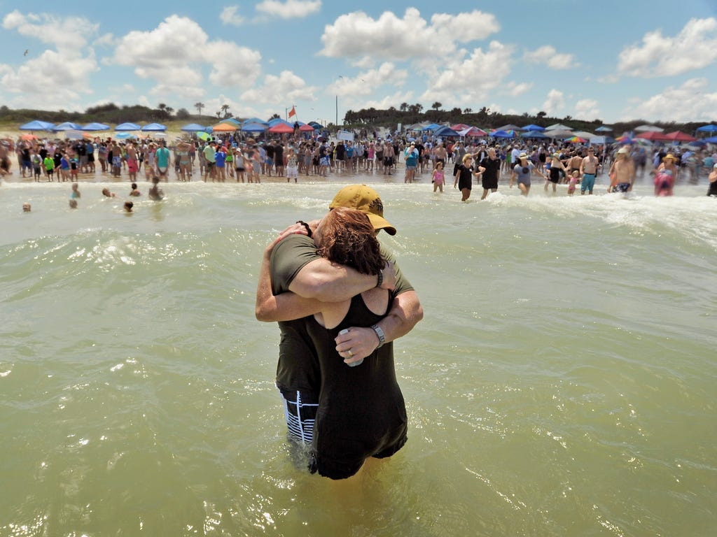 Tammy Smith, center right, gets a hug after being baptized as church members watch from the packed beach in Jacksonville. The Church of Eleven22 held their annual beach baptism in the surf off Hanna Park.