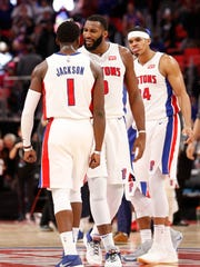 Pistons guard Reggie Jackson celebrates with center Andre Drummond (0) and forward Tobias Harris (34) after making a 3-pointer in the fourth quarter of the team's 111-104 win over the Hawks on Nov. 10, 2017 at Little Caesars Arena.