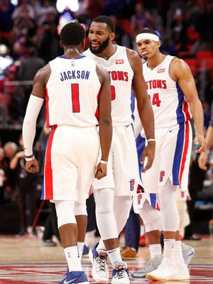 Pistons guard Reggie Jackson celebrates with center Andre Drummond (0) and forward Tobias Harris (34) after making a 3-point basket in the fourth quarter of the team's 111-104 win over the Hawks on Friday.