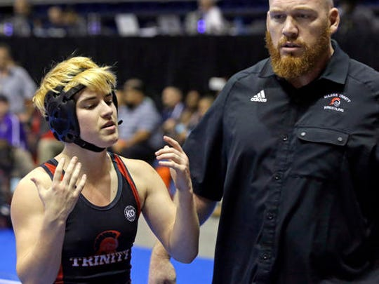 Mack Beggs, left, a transgender wrestler from Euless Trinity High School, stands with his coach Travis Clark during a quarterfinal match against Mya Engert, of Amarillo Tascosa, during the State Wrestling Tournament, Friday, Feb. 24, 2017, in Cypress, Texas. Beggs was born a girl and is transitioning to male but wrestles in the girls division.