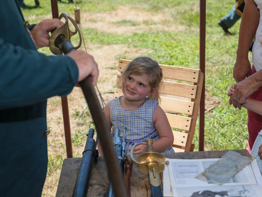 Fianna Harrington, 3, of Brick, center, listens to a soldier at the Civil War encampment by the 61st New York Regiment of Civil War Soldiers at Brick Historical Society's Haven's Homestead Museum on August 7, 2016.