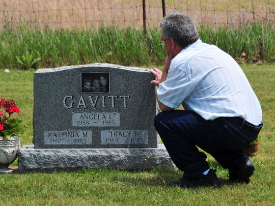 In this June 6, 2012, photo provided by John Masson, David Gavitt visits the grave of his wife and two daughters in Ionia County, Mich., immediately after he was released from prison after 26 years.