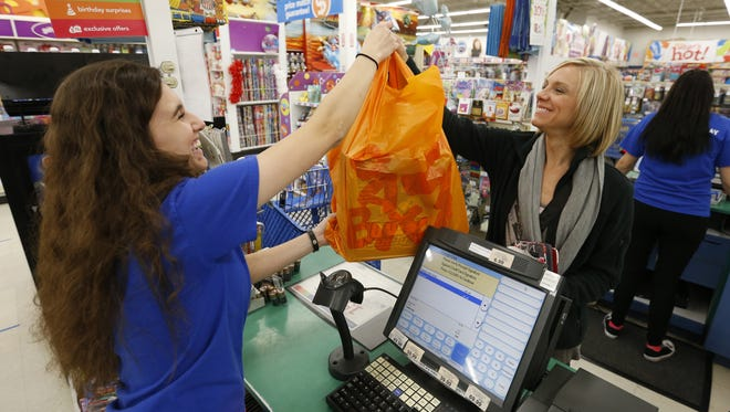 Cashier Samra Vatres hands Jessica Danilson of Cedar Rapids her purchases Friday, Nov. 27, 2015, as shoppers take advantage of early-morning deals during Black Friday at Toys R Us in Clive.