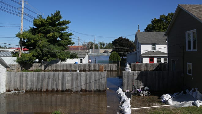 Floodwater from the Cedar River flows in to the backyards of houses in Vinton, Iowa, including Jack and Peggy Harris' home (white home on the right) on Monday, Sept. 26, 2016. Jack and Peggy said they did not think their home would flood again, because it's in the 500-year flood plain.