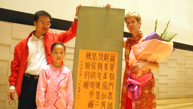 Lea Gentile, right, a U.S. pianist and music teacher, receives flowers and a gift of calligraphy after performing at the Happy 60th Birthday China Concert in Tianjin, China, in October 2009. Gentile, 64, a Tianjin resident for 14 years, hopes proposed changes to China's green card system will make it easier to secure permanent residence.