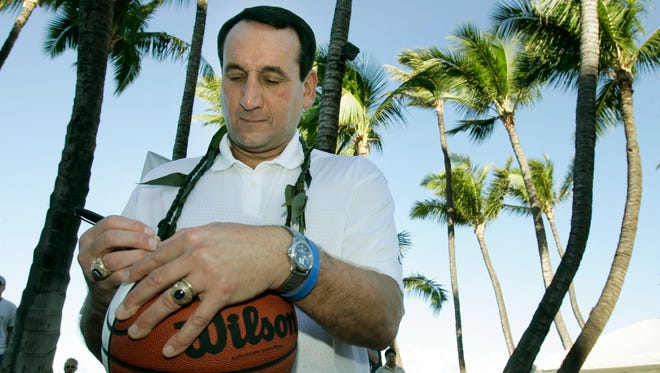 Duke coach Mike Krzyzewski signs a basketball after winning a charity free throw shooting contest before the start of the EA Sports 25th Maui Invitational.