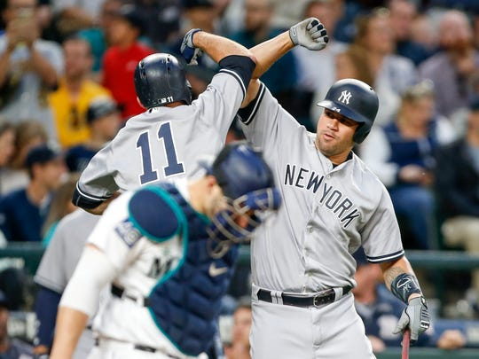 New York Yankees catcher Gary Sanchez (24) greets left fielder Brett Gardner (11) following a solo home run by Gardner against the Seattle Mariners during the sixth inning at Safeco Field.