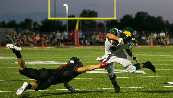 A Williams Field defender takes down Garrett Means after a catch in Williams Field's 31-7 victory Friday.