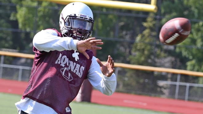 Aquinas DE/LB Jamir Jones eyes in a reception during drills on the opening day of high school football practice Aug. 17, 2015.