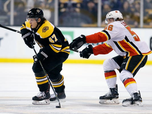 Calgary Flames' Ryan Lomberg (56) battles Boston Bruins' Torey Krug (47) for the puck during the first period of an NHL hockey game in Boston, Tuesday, Feb. 13, 2018. (AP Photo/Michael Dwyer)