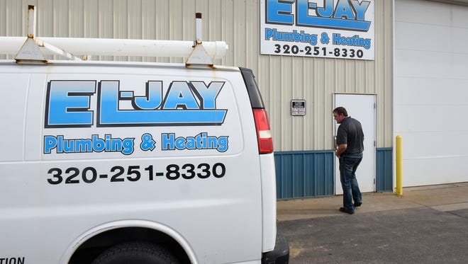 Bryant Fritz walks into a storage building Monday, Nov. 7, at El-Jay Plumbing & Heating in St. Cloud.