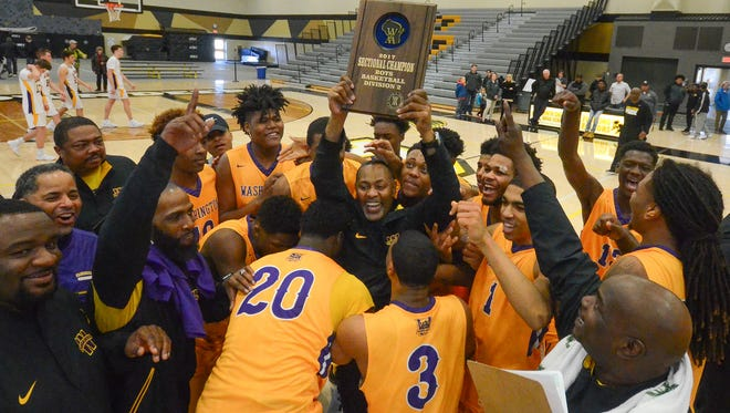 Milwaukee Washington High School basketball players swarm coach Freddie Riley as he hoists the sectional champion's plaque after the Purgolders beat New Berlin Eisenhower, 52-43, Saturday, March 11, 2017, at Brown Deer High School.