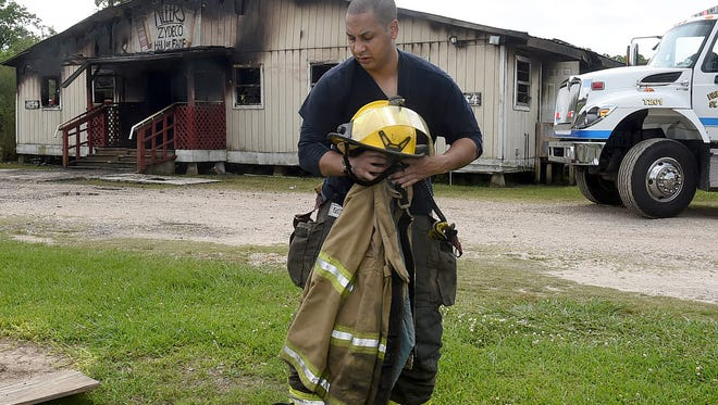Miller's Zydeco Hall of Fame looms in the background as a firefighter gathers his gear after battling a fire that destroyed the famous dance hall Wednesday.