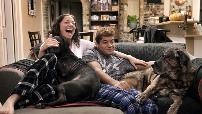 Rachel Eckman jokes with her foster son, Adrian Cobos, 16, in their East El Paso home with her dogs, Jack and Layla. Eckman said preparing to become a foster parent was difficult but completely worth it.