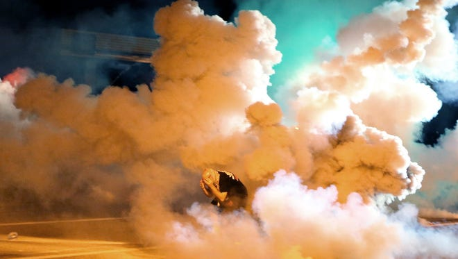 """In this Aug. 13, 2014 file photo a protester takes shelter from smoke billowing around during protests against the shooting of 81-year-old Michael Brown in Freguson, Mo. A federal judge on Thursday, Dec. 11, 2014, granted a temporary restraining order on behalf of protesters involved in the demonstrations that requires police to warn crowds of impending use of tear gas and provide """"reasonable"""" time for people to disperse before tear gas is deployed. The ruling applies only to Missouri."""
