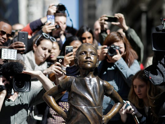 """People stop to photograph the Fearless Girl statue when it was in New York. The statue was created by Lewes artist Kristen Visbal and installed by investment firm State Street Global Advisors. An inscription at the base reads, """"Know the power of women in leadership. She makes a difference."""""""