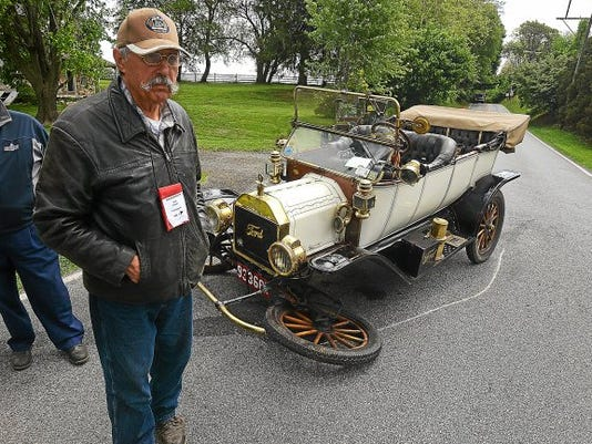 Paul Povinelli, of Trumansburg N.Y., the driver of the Model T, watches as crews remove the Kia from the storm ditch. He was taking part in a driving event with 80-plus other vehicles from the early 20th century when the crash occurred.