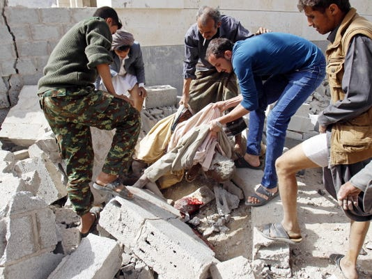 People carry the body of a man killed in a Saudi-led airstrike against Iran-allied Shiite rebels, known as Houthis, that hit a site of a weapons cache in Yemen's capital, Sanaa, Monday, April 20, 2015. The strikes on Yemen's rebel-held capital on Monday caused massive explosions that shattered windows, sent residents scrambling for shelter and killed a local TV presenter.